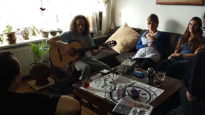 Karma Kitchen. Vier jongeren zitten op de bank waarvan twee gitaar spelend